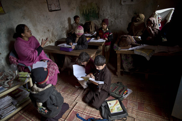 Afghan refugees and internally displaced Pakistani schoolchildren attend a class at a makeshift school on the outskirts of Islamabad, Pakistan, Friday, February 20, 2015. (Photo by Muhammed Muheisen/AP Photo)