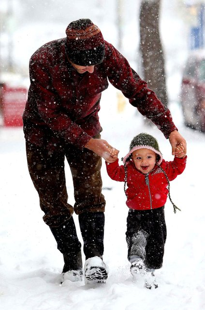 Julian Tucci, 1, enjoys his first snowfall with his father Jeremy, in Eugene, Oregon, on December 6, 2013. (Photo by Brian Davies/The Register-Guard)