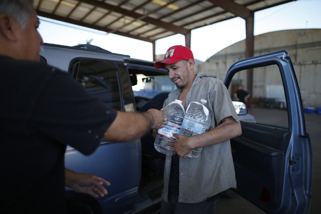 Pastor Frankie Olmedo, 56, (L) who volunteers four hours a day to hand out water, hands bottles to Luis Bocanegra, 35, in Porterville, October 14, 2014. (Photo by Lucy Nicholson/Reuters)