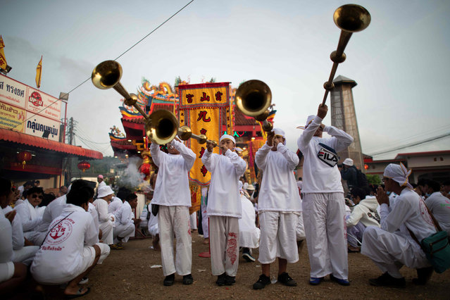 Devotees of the Loem Hu Thai Su shrine parade during the annual Vegetarian Festival in Phuket on October 12, 2018. The festival begins on the first evening of the ninth lunar month and lasts for nine days, with many religious devotees slashing themselves with swords, piercing their cheeks with sharp objects and committing other painful acts to purify themselves, taking on the sins of the community. (Photo by Jewel Samad/AFP Photo)