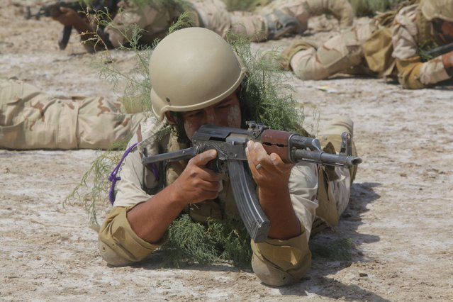 A member from the Iraqi security forces carries his weapon during military training in Jurf al-Sakhar, Iraq April 9, 2015. (Photo by Alaa Al-Marjani/Reuters)