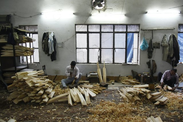 In this photograph taken on December 14, 2016, an Indian craftsman works on unfinished cricket bats in a factory in Meerut, some 70kms north-east of New Delhi. (Photo by Dominique Faget/AFP Photo)