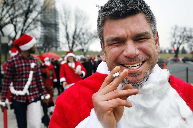 A reveler dressed as Santa Claus enjoys a cigarette as he participates in the Santarchy mass gathering in Washington. (Photo by Jonathan Ernst/Reuters)