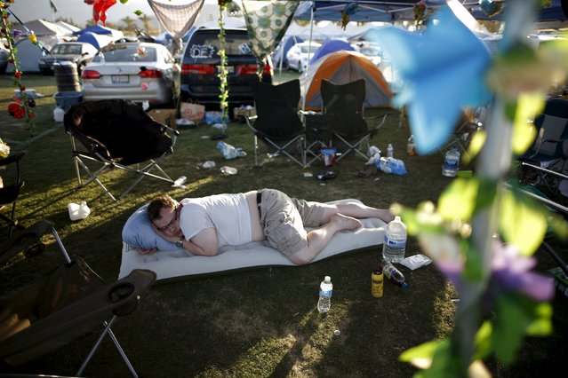 A man takes a nap in the car camping area at the Coachella Valley Music and Arts Festival in Indio, California April 11, 2015. (Photo by Lucy Nicholson/Reuters)