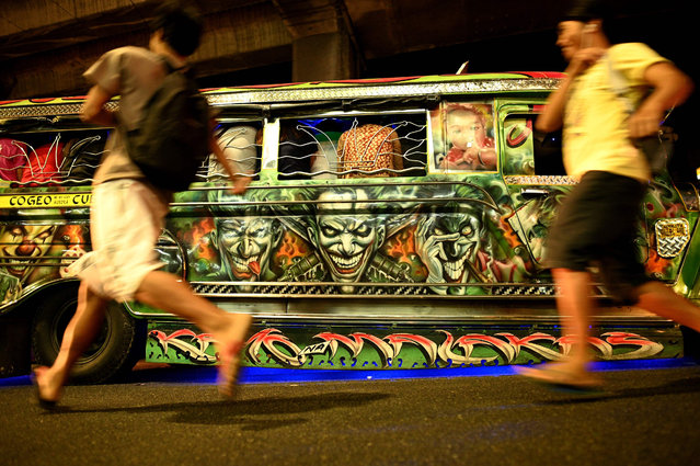 This picture taken on January 14, 2019 shows custom artwork on the side of a jeepney as commuters run to catch a ride on the vehicle during rush hour in Manila, Philippines. (Photo by Noel Celis/AFP Photo)