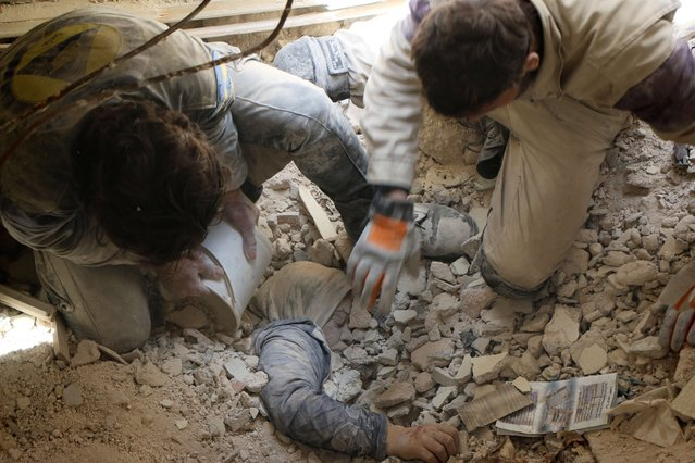 Syrian emergency services personnel try to pull a woman out from under the rubble of a building following a reported barrel bomb attack by government forces on the rebel held Bustan al-Qasr district in the east of the northern Syrian city of Aleppo on April 13, 2015. (Photo by Zein Al-Rifai/AFP Photo)