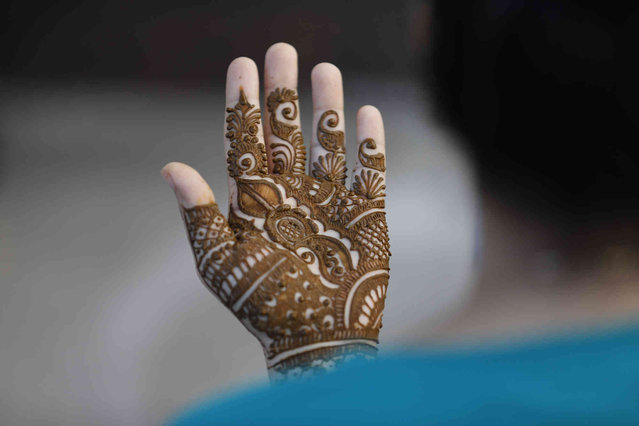A woman holds her henna-decorated hand to dry on the eve of the Hindu festival of Teej in Prayagraj, India, Wednesday, September 8, 2021. During this festival married women observe a day-long fast for the longevity of their husbands, while unmarried women observe a fast praying for a good husband. (Photo by Rajesh Kumar Singh/AP Photo)