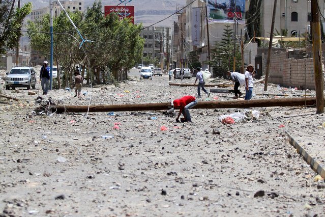 A boy searchs about a toartillery shell in ground at a damaged street, caused by an April 20 air strike that hit a nearby army weapons depot, in Sanaa April 21, 2015. (Photo by Mohamed al-Sayaghi/Reuters)