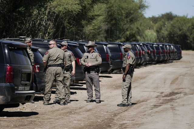 Texas Department of Public Safety officials stand near a lineup or vehicles parked near an encampment under the Del Rio International Bridge where migrants, many from Haiti, have been staying after crossing the Rio Grande, Thursday, September 23, 2021, in Del Rio, Texas. (Photo by Julio Cortez/AP Photo)