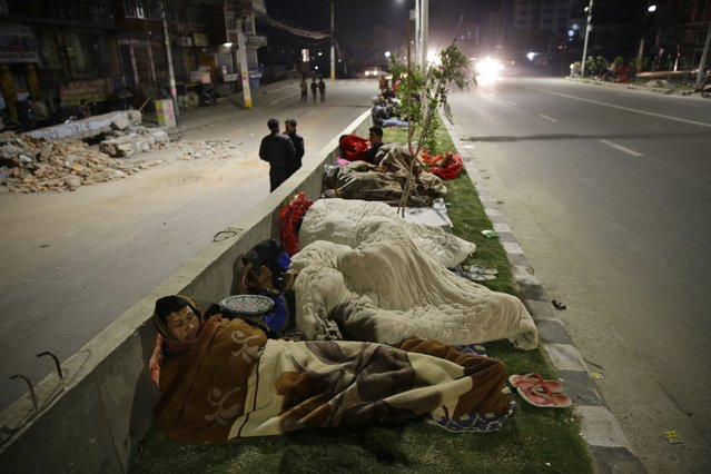 People sleep outside on a street a in Kathmandu, Nepal, 25 April 2015 following a massive earthquake. Hundreds of people died and many more were feared trapped in rubble on 25 April 2015 after a magnitude-7.9 earthquake devastated Nepal's capital and triggered a deadly avalanche on Mount Everest. (Photo by Narendra Shrestha/EPA)