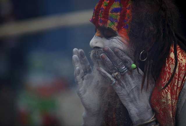 A Hindu holy man, or sadhu, smears ashes on his face during the Shivaratri festival at the premises of Pashupatinath Temple in Kathmandu, Nepal, March 7, 2016. (Photo by Navesh Chitrakar/Reuters)