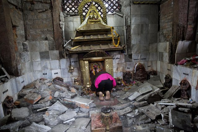 A Hindu Nepalese woman offers prayers at Indrayani temple, that was damaged in Saturday's earthquake, in Kathmandu, Nepal, Monday, April 27, 2015. (Photo by Bernat Armangue/AP Photo)