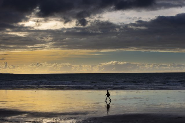 A person walks on Orewa Beach in Auckland, New Zealand, on June 5, 2021. New Zealand has recorded its warmest June since recordkeeping began, as ski fields struggle to open and experts predict shorter southern winters in the future. (Photo by Brett Phibbs/New Zealand Herald via AP Photo)