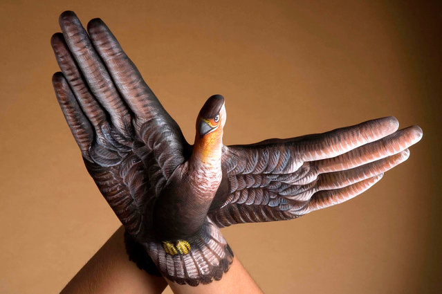 Models poses with their arm after it was painted by body artist Guido Daniele