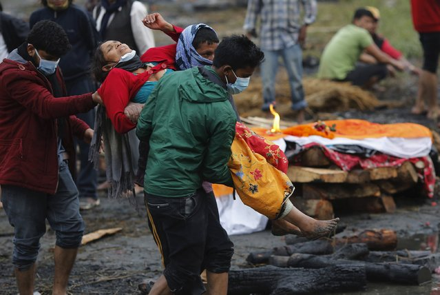 People carry a woman who fainted after performing the last rites of her family members, who died in Saturday's earthquake, along a river in Kathmandu, Nepal April 28, 2015. (Photo by Adnan Abidi/Reuters)