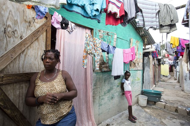 In this December 2, 2016 photo, Adrienne St. Fume stands outside her shelter in the Delmas tent camp set up set up nearly seven years for people displaced by the 2010 earthquake, in Port-au-Prince, Haiti. The mother of three said she figured the shack built of plywood scraps and plastic tarp would be temporary as they and the rest of Port-au-Prince recovered from the earthquake. But St. Fume has yet to find a way out. (Photo by Dieu Nalio Chery/AP Photo)