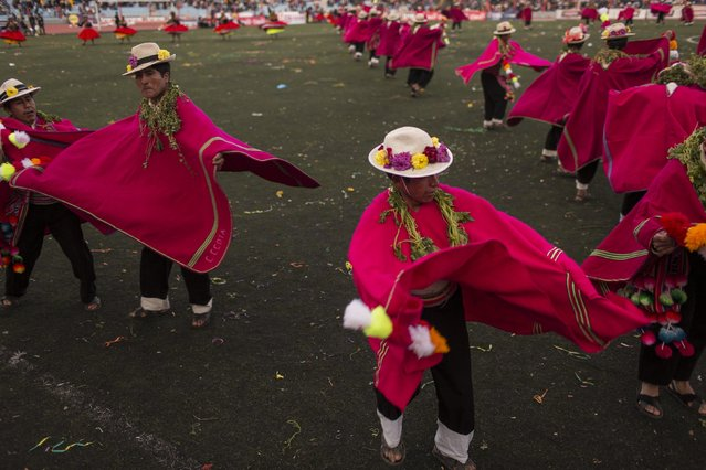In this January 29, 2017 photo, dancers perform during Virgin of Candelaria celebrations in Puno, Peru. Some dances gesture toward everyday village activities such as grazing llamas or shearing animals. Others depict the Spanish conquest or the conscription of villagers as soldiers. (Photo by Rodrigo Abd/AP Photo)