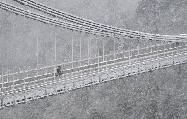 A person cycles over the Clifton Suspension Bridge and Avon Gorge in Bristol during snowfall in southwest Britain, February 1, 2019. (Photo by Toby Melville/Reuters)