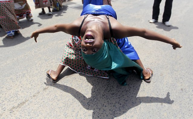 A supporter of Burundi's President Pierre Nkurunziza dances on the street after their ruling Conseil National pour la Defense de la Democratie – Forces pour Defense de la Democratie (CNDD-FDD) party congress meeting in the capital Bujumbura, April 25, 2015. Burundi's ruling party chose President Nkurunziza to run for a third five-year term on Saturday, a move critics say is unconstitutional and may trigger unrest in the east African country. (Photo by Thomas Mukoya/Reuters)