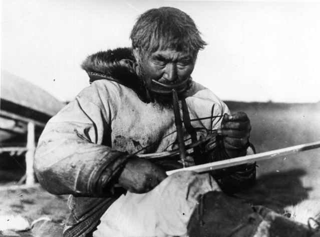 An Inuit carpenter at work using a traditional bow drill which he holds with his mouth and turns with a string, circa 1910. (Photo by Earl Rossman/General Photographic Agency/Getty Images)