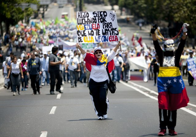 "An opposition demonstrator with a Venezuelan national flag draped around her shoulders, holds a sigh with a message that reads in Spanish; ""Son, I keep fighting for Venezuela, so that you don't leave it, or sink with it"", during a May Day march in Caracas, Venezuela, Friday, May 1, 2015. (Photo by Ariana Cubillos/AP Photo)"