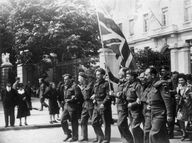 8th May 1945: British troops in Paris celebrate VE Day by parading a Union Jack through the streets in triumph.  (Photo by Keystone/Getty Images)