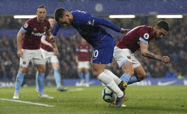 Chelsea's Eden Hazard, left, vies for the ball with West Ham's Manuel Lanzini during the English Premier League soccer match between Chelsea and West Ham at Stamford Bridge stadium in London, Monday, April 8, 2019. (Photo by Alastair Grant/AP Photo)
