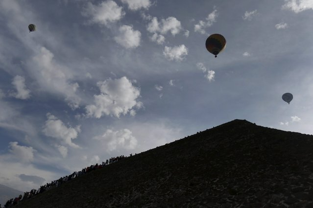 Hot air balloons float above people standing in line to climb the Pyramid of the Sun and welcome the spring equinox in the pre-hispanic city of Teotihuacan, on the outskirts of Mexico City, Mexico, March 20, 2016. (Photo by Edgard Garrido/Reuters)