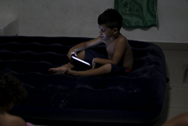 Cuban migrant child looks at a tablet in one of the rooms at an old hotel used as a provisional shelter in Paso Canoas, at the border with Costa Rica, in Panama March 21, 2016. (Photo by Carlos Jasso/Reuters)