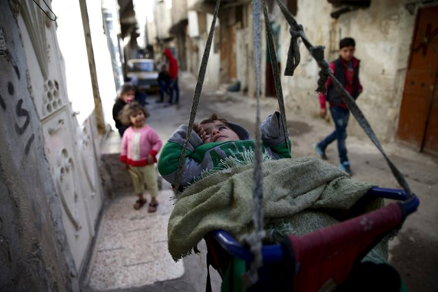 A child rests in a cradle along a street in the rebel-held Tishreen neighborhood of Damascus, Syria March 14, 2016. (Photo by Bassam Khabieh/Reuters)