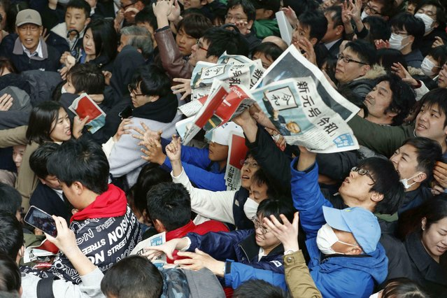 """People reach out for copies of newspaper extra edition reporting the name of new era """"Reiwa"""" in Osaka, Monday, April 1, 2019. The name of the era of Japan's soon-to-be-emperor Naruhito will be """"Reiwa"""", the government announced Monday. (Photo by Juntaro Yokoyama/Kyodo News via AP Photo)"""
