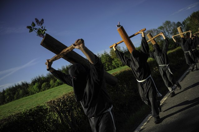 """Masked penitents holds their crosses  during spring """"Romeria Cruceros de Arce"""", while they walk alongside Villanueva de Arce and Roncesvalles northern Spain Sunday, May 10, 2015. (Photo by Alvaro Barrientos/AP Photo)"""