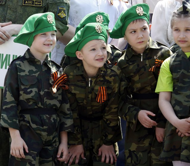 Children wearing specially made uniforms, watch the so-called Kid Parade in Rostov-on-Don, Russia, Thursday, May 14, 2015. Hundreds of children walked past medal-bedecked veterans in a parade marking the 70th anniversary of World War II victory. (Photo by AP Photo/Stringer)