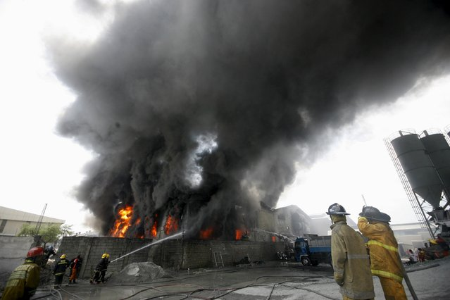 Firefighters attempt to control a raging fire at a factory that manufactures slippers in Valenzuela City, north of Manila May 13, 2015. Three were confirmed dead and about 65 people are still missing after a fire that razed through the factory that reached Task Force Charlie, prompting firefighters from nearby provinces to respond, local media reported. (Photo by Al Falcon/Reuters)