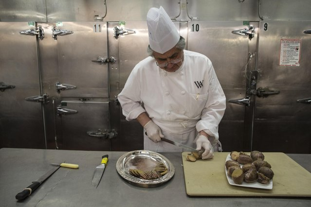 A chef slices up bull testicles in the kitchen before the 110th Explorers Club Annual Dinner at the Waldorf Astoria in New York March 15, 2014. (Photo by Andrew Kelly/Reuters)