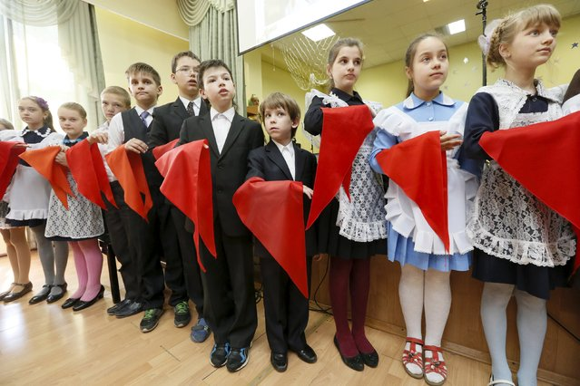 Children, holding red neckerchiefs, a symbol of the Young Pioneer Organisation, line up during a ceremony for the inauguration of 45 newly adopted members on the day of its anniversary at school-lyceum number 12 in the Siberian city of Krasnoyarsk, Russia, May 19, 2015. (Photo by Ilya Naymushin/Reuters)