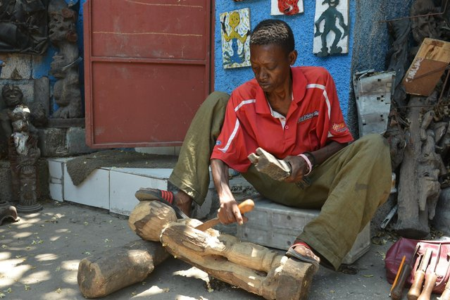 In this April 2, 2016 photo, sculptor Jean Robert Palanquet carves on a piece of wood in an open-air museum and art workshop off a trash-strewn street cutting through some of the poorest neighborhoods in Port-au-Prince, Haiti. Palanquet is a member of a collective of Haitian artists called Atis Rezistans who have become celebrated in the international art world by creating sculptures out of scrapped car parts, old wood, cast-off toys and even human skulls found scattered outside crumbling mausoleums. (Photo by David McFadden/AP Photo)