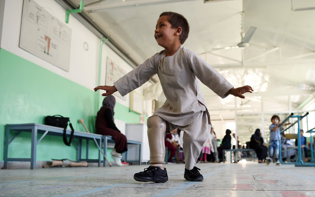 Ahmad Sayed Rahman, a five-year-old Afghan boy who lost his right leg when he was hit by a bullet in the crossfire of a battle, dances with his prosthetic leg at the International Committee of the Red Cross (ICRC) hospital for war victims and the disabled, in Kabul on May 7, 2019. With his hands in the air and an infectious grin spreading from ear to ear, a young Afghan boy whirls around a Kabul hospital room on his new prosthetic leg. The boy, five-year-old Ahmad Sayed Rahman, has become a social media star in Afghanistan and beyond after a short video of him effortlessly dancing on his new limb was published this week on Twitter. (Photo by Wakil Kohsar/AFP Photo)