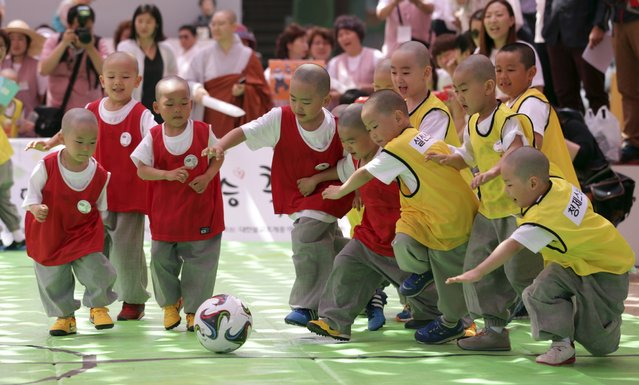 Shaven-headed children who entered temples to have an experience of monks' life for weeks, play Dongjasung (little monk) soccer at Jogye temple in Seoul, South Korea, Thursday, May 14, 2015. The Dongjasung soccer match is one of the events to celebrate Buddha's upcoming 2,559th birthday on May 25 and to publicize Korean Buddhism. (Photo by Lee Jin-man/AP Photo)