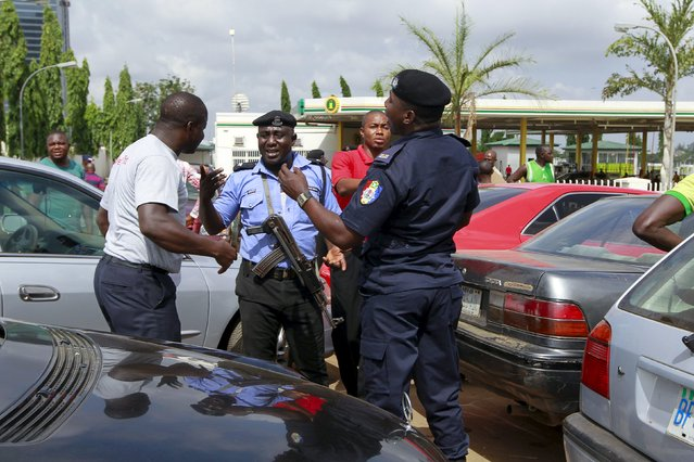 Security peronnel speak with a motorist as they face fuel scarcity outside the NNPC mega petrol station in Abuja, Nigeria May 25, 2015. (Photo by Afolabi Sotunde/Reuters)