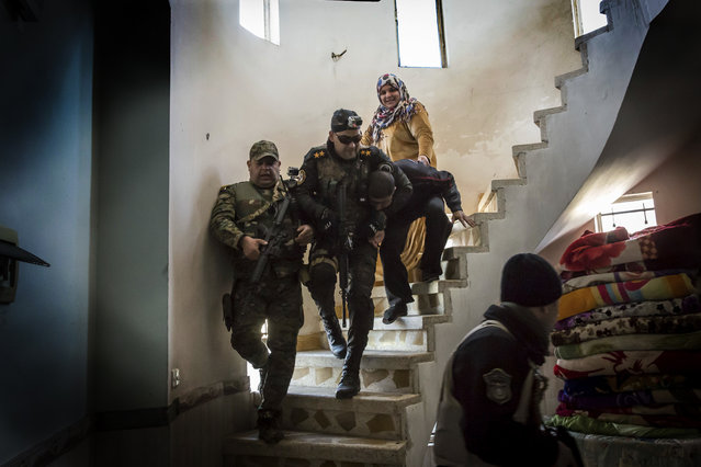 In this Tuesday, February 21, 2017 photo, Iraqi security forces drag a suspected IS fighter down a spiral staircase after raiding his house in the liberated eastern part of Mosul. The suspects are identified via intelligence gathered from information received from other civilians in the city. (Photo by John Beck/AP Photo)