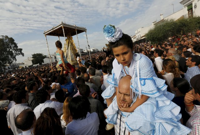 A girl wearing a rociera dress is carried over shoulders of a man during Virgin of El Rocio procession around the shrine of El Rocio in Almonte, southern Spain, May 25, 2015. (Photo by Marcelo del Pozo/Reuters)