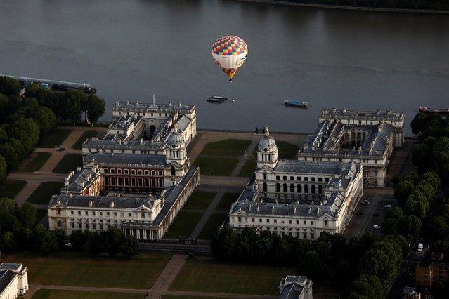 A hot air balloon flies over Greenwich Maritime Museum during the Lord Mayor's Hot Air Balloon Regatta, in London, June 9, 2019. (Photo by Simon Dawson/Reuters)