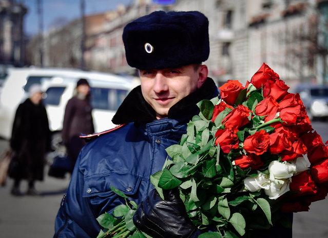 A traffic policeman gives flowers to female drivers ahead of International Women's Day on the citys Central Sqare in Vladivostok, Russia on March 7, 2017. (Photo by Yuri Smityuk/TASS via Getty Images)