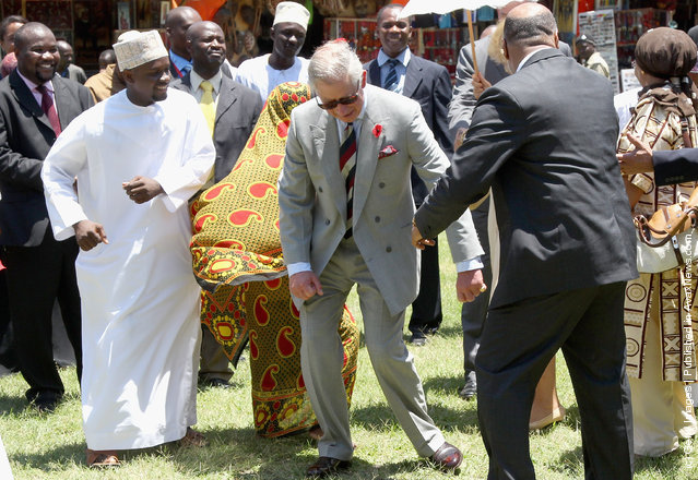 Camilla, Duchess of Cornwall and Prince Charles, Prince of Wales take part in a chapauringe dance in Stone Town Old Fort