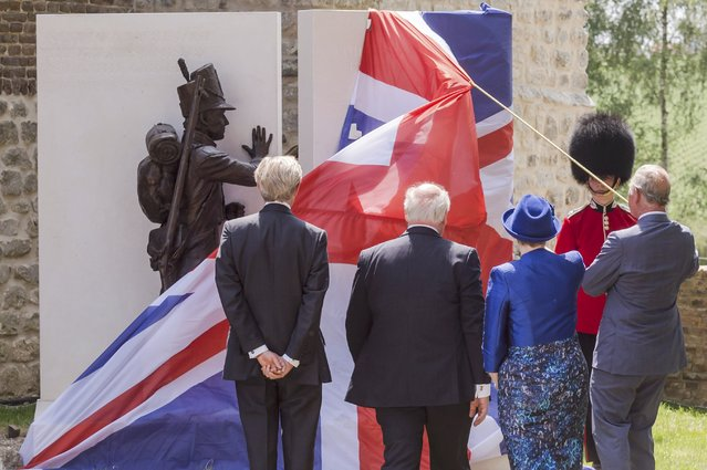 Britain's Prince Charles (R) holds a rope as he unveils a monument during a ceremony for the opening of the Hougoumont farm as part of the bicentennial celebrations for the Battle of Waterloo, near Waterloo, Belgium June 17, 2015. The commemorations for the 200th anniversary of the Battle of Waterloo will take place in Belgium on June 19 and 20. REUTERS/Geert Vanden Wijngaert/Pool