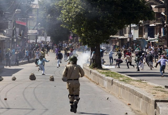Kashmiri Muslims protesters run for cover as tear gas shells explode near them during a protest in Srinagar, Indian-controlled Kashmir, Saturday, June 27, 2015. (Photo by Dar Yasin/AP Photo)