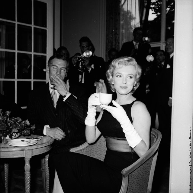 1956: American film star Marilyn Monroe (1926 - 1962) sits next to British thespian Laurence Olivier (1907 - 1989) at a press conference at the Savoy Hotel, London