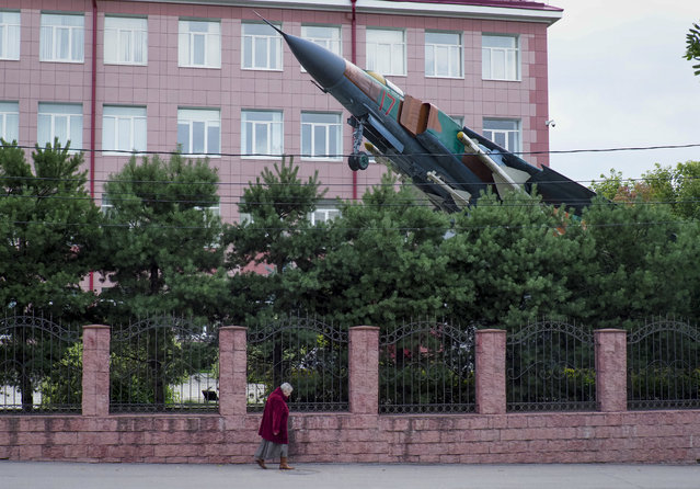 A woman walks past a MIG-23 Soviet fighter jet mounted as a monument at the Research Institute of Information Technologies in the town of Tver, 180 km (111 miles) north-west of Moscow, Russia, Sunday, August 4, 2019. (Photo by Dmitri Lovetsky/AP Photo)