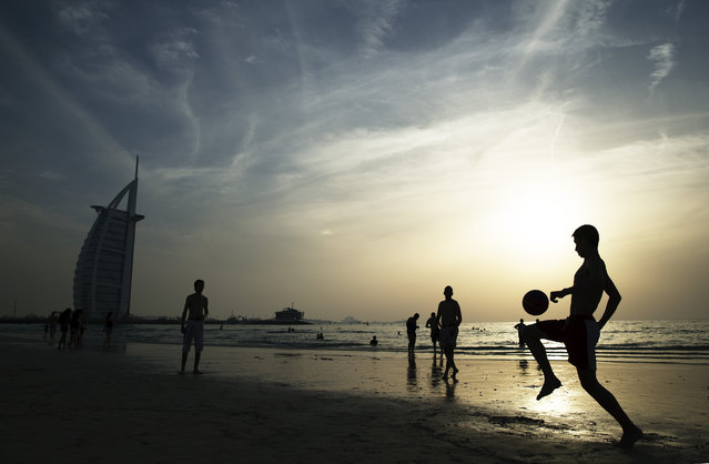 People enjoy Umm Suqeim Beach near the luxury Burj Al Arab Hotel on April 17, 2014 in Dubai, United Arab Emirates. (Photo by Warren Little/Getty Images)